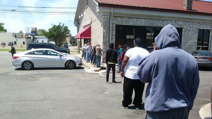 Folks line up for booze at the Alabama State Store following social distancing guidelines.