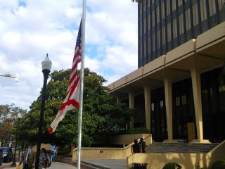 The flags fly at half staff in front of the Madison County Courthouse where an empty space remains in place of Huntsville's confederate monument. The flags have been lowered to honor Mayor Tommy Battles wife Eula, who will be laid to rest today, also in Maple Hill Cemetery.