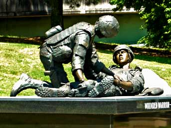A medic attends to a wounded warrior at a new display staged at Huntsville Veteran's Memorial.